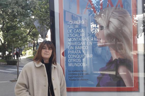 "Carmen Gayà al lado de un cartel de la campaña de juguetes no sexistas "" title="